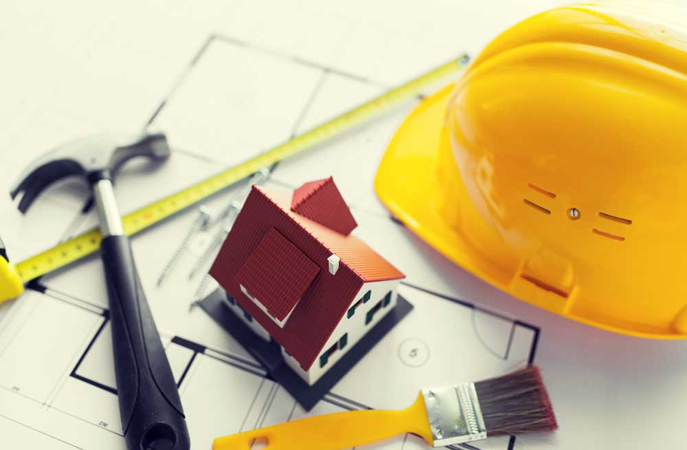 Blueprint for new house plans with a construction hat, hammer and miniature house
