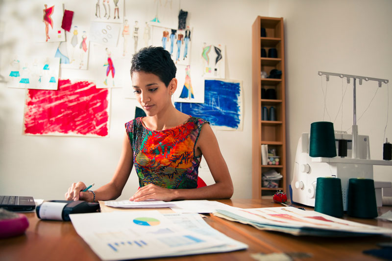 Self-employed woman doing her budget in her fashion design office