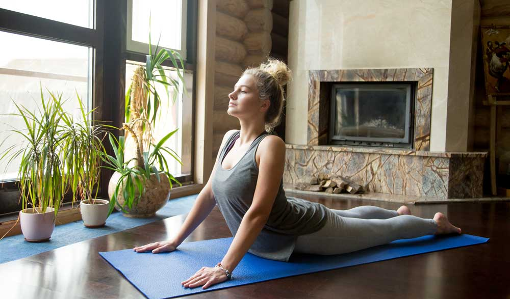 Flexible woman practicing yoga in her new home
